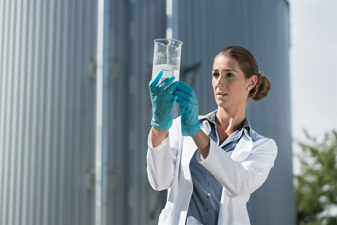 Laboratory technician looking at water sample taken from sewage treatment plant